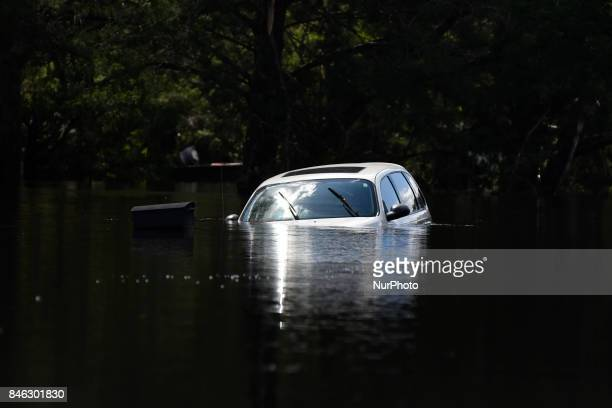 A car sits submerged in flood waters along a road in Middleburg Florida US on September 12 2017 Seven million utility customers across the US...