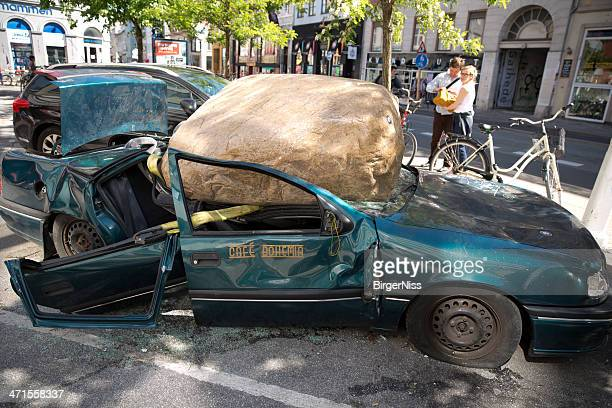 Car smashed by huge rock