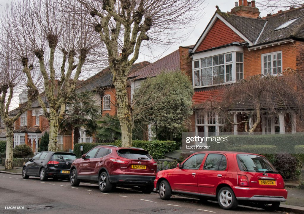 Car sparked in front of  typical houses north of London, UK : Stock Photo