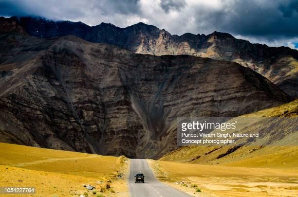 a car speeding on a mountain road surrounded by himalayan mountain range - paisajes de india fotografías e imágenes de stock