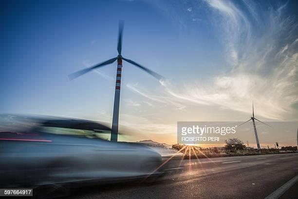 Car speeding past wind turbines, Cagliari, Sardinia, Italy