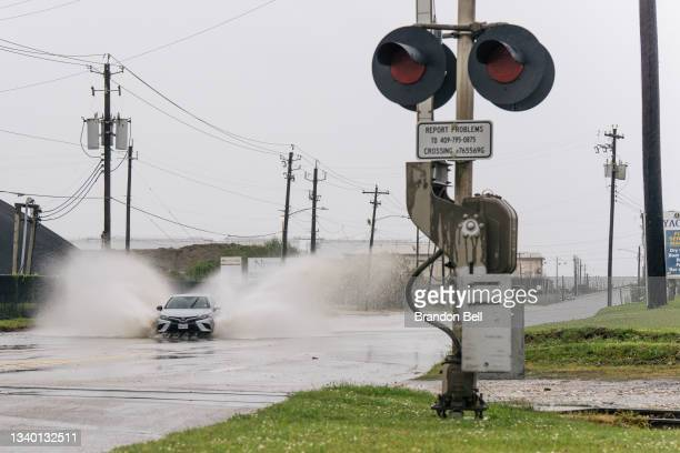 Car speeds through a flooded street ahead of the Tropical Storm Nicholas on September 13, 2021 in Galveston, Texas. A hurricane watch is in effect as...