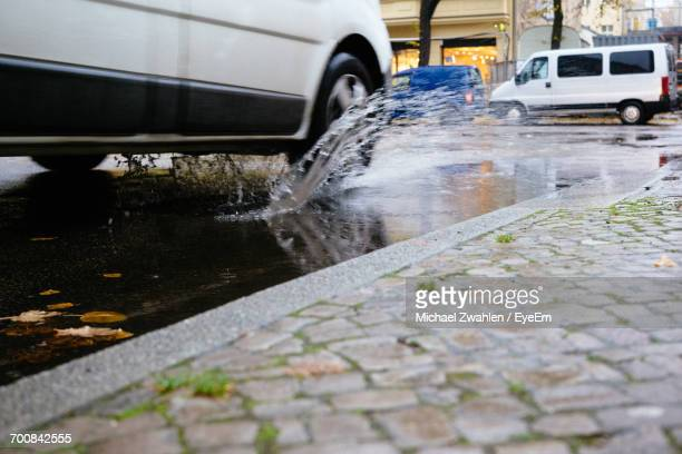 Car Splashing Water From Puddle In City