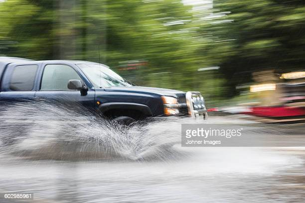 Car splashing water on road