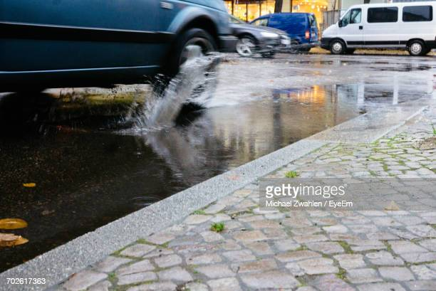 Car Splashing Water While Moving On Puddle