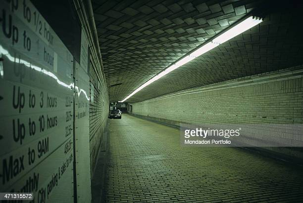 A car standing in the tunnel of a pay and display underground car park New York 1990s