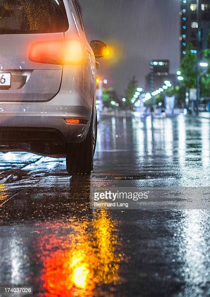 Car standing on street in the rain, rear view