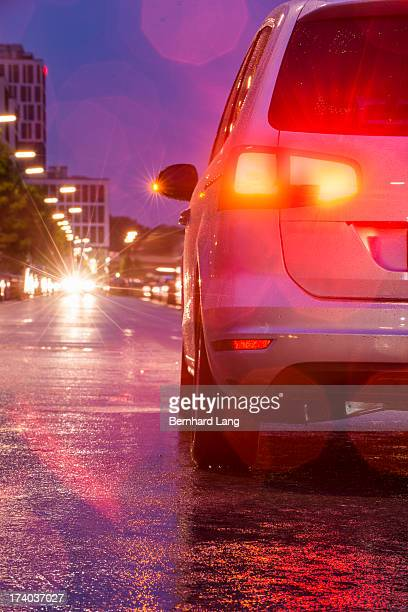 Car standing on urban road, rear view, dusk