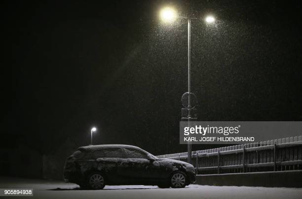 A car stands on a parking site as snow falls on Apfeltrang southern Germany on January 17 2018 / AFP PHOTO / dpa / KarlJosef Hildenbrand / Germany OUT