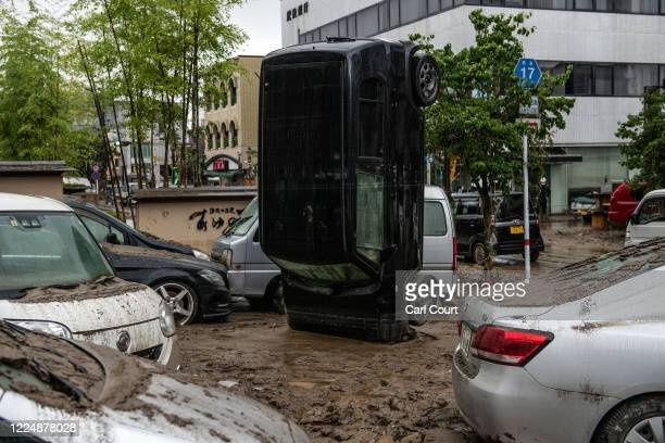 Car stands on its front after being upturned by flooding after the nearby Kuma River burst its banks, on July 5, 2020 in Hitoyoshi, Japan. Around 16...