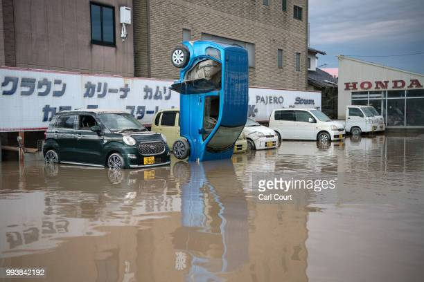 A car stands on its front following heavy flooding on July 8 2018 in Kurashiki near Okayama Japan Over 70 people have died and dozens are missing in...