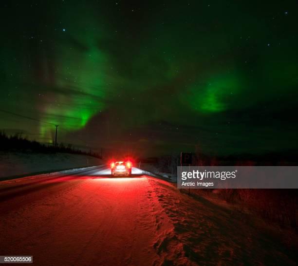 Car stopped on road beneath the Aurora Borealis
