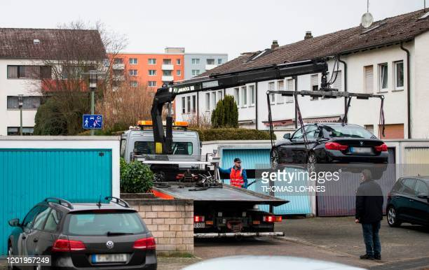 A car that allegdgedly belongs to a supect in a killing is lifted on a truck near the home of the suspect in Hanau western Germany on February 20...