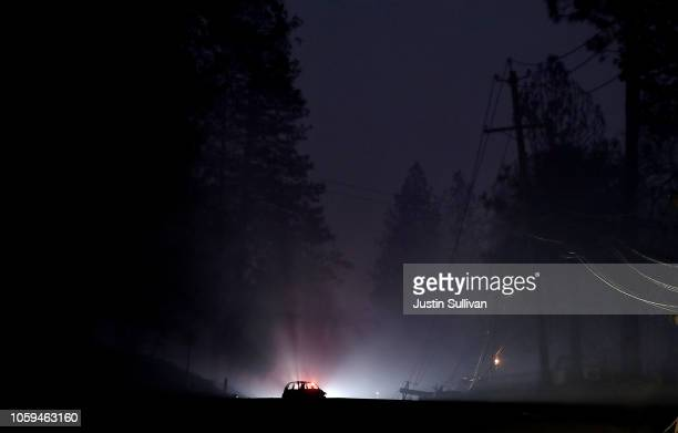 A car that was burned by the Camp Fire is illuminated by headlights as it sits in the middle of a road on November 8 2018 in Paradise California...