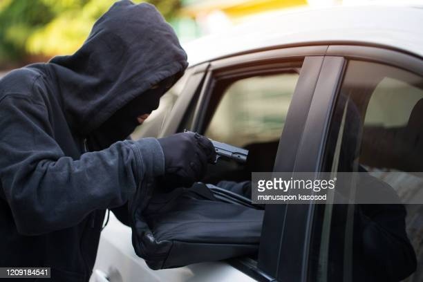 car theft - thief trying to break into the vehicle. - 1910 1919 stock pictures, royalty-free photos & images