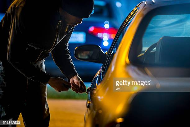 car thief using a screwdriver to brake into a car - thief stock pictures, royalty-free photos & images