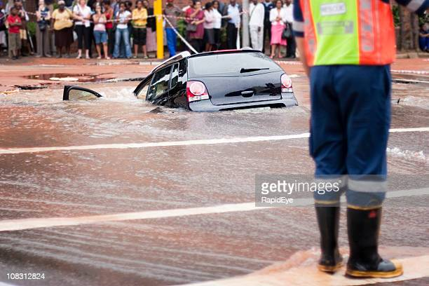 Car tips into flooded pothole, rear view