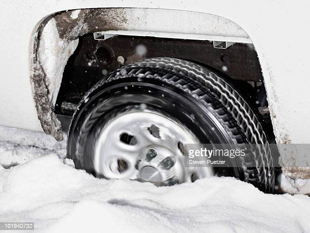Car tire stuck in snow spinning tires