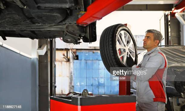 car tire - vehicle part removing and installing in the auto repair shop - tire vehicle part stock pictures, royalty-free photos & images
