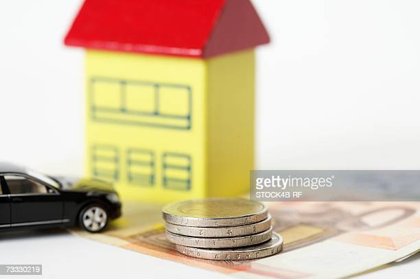 Car, toy house and a stack of coins on Euro banknotes