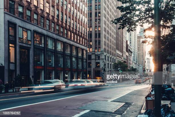 car traffic at dusk , blurred motion in midtown manhattan - midtown manhattan stock pictures, royalty-free photos & images