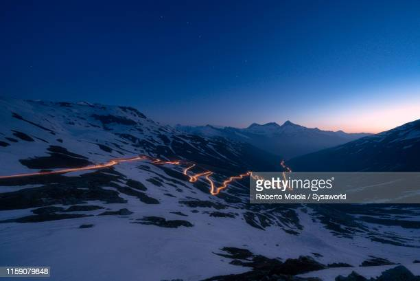 car trail lights on bends of splugen pass, switzerland - schweiz stock-fotos und bilder
