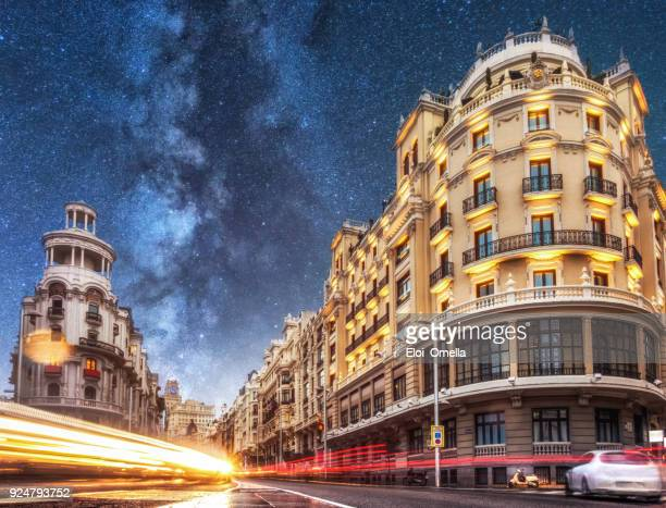 car trails in gran via at night with milky way. madrid. spain