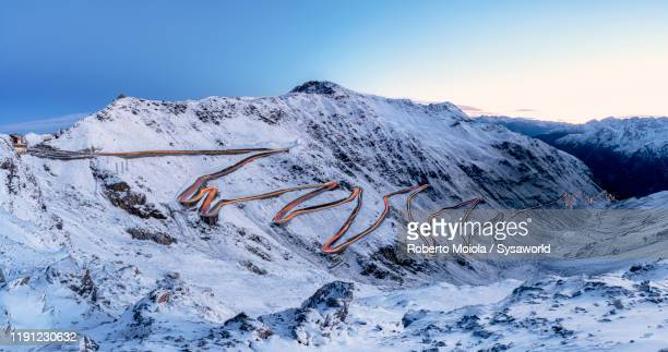 car trails lights on bends of stelvio pass mountain road, south tyrol, italy - ロンバルディア州 ストックフォトと画像