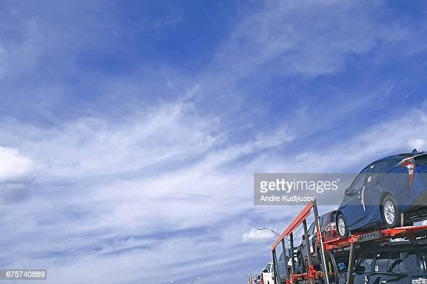 Car transporter against blue sky