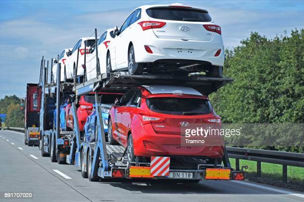 car transporter driving on the highway - compact car stock photos and pictures