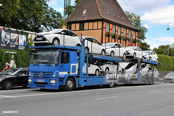 car transporter driving on the street - car transporter stock photos and pictures