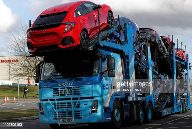 A car transporter loaded with new Honda vehicles is driven out of the Honda manufacturing plant in Swindon southwest England on February 19 2019...
