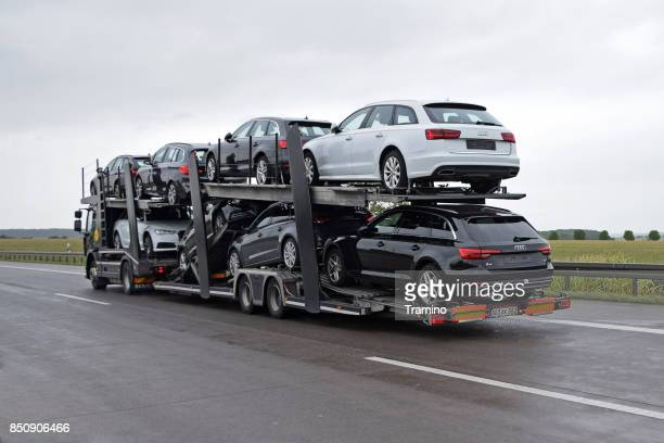 Car transporter with Audi and BMW vehicles driving on the highway