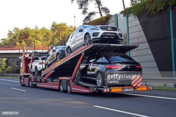 car transporter with mercedes-benz vehicles driving on the highway - car transporter stock photos and pictures