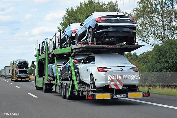 car transporters driving on the highway - car transporter stock photos and pictures