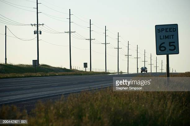 car traveling on road, sunrise - speed limit sign stock photos and pictures