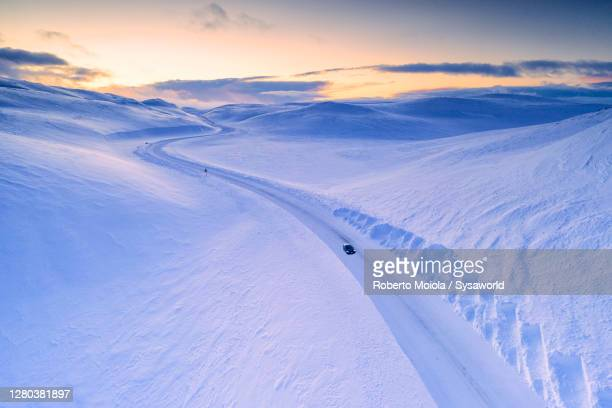 car traveling on scenic road in the snow at sunset, finnmark, norway - idyllic stock pictures, royalty-free photos & images