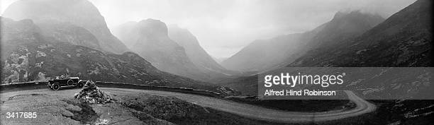 Car travelling along a misty road through the Pass of Glencoe in the Scottish Highlands. Glencoe is considered to be one of the wildest glens and is...