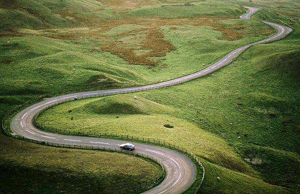Car Travelling Down Snaking Road Through Grazing Land Of The Peak District, United Kingdom Wall Art