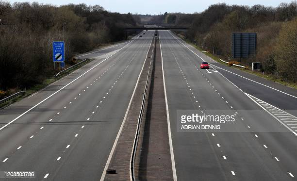 Car travels along the almost deserted M3 motorway near Fleet, south west of London on March 29 as life in Britain continues during the nationwide...