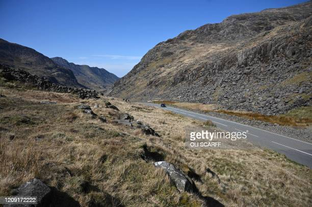 Car travels along the near-deserted A4086 at Pen-y-Pass, near to Mount Snowdon, in north Wales on April 5, 2020 as the warm weather tests the...