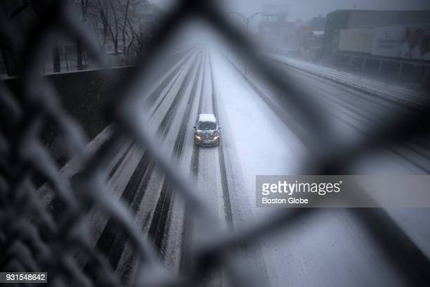 A car travels westbound on the Massachusetts Turnpike near Fenway Park in Boston during the third nor'easter storm to hit the region in two weeks on...