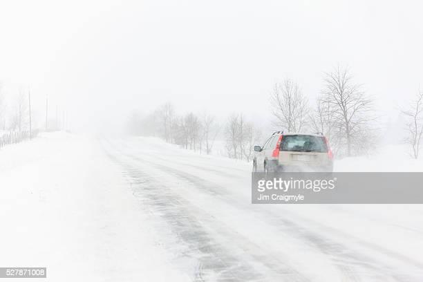 Car travling along rural road in a snow storm.