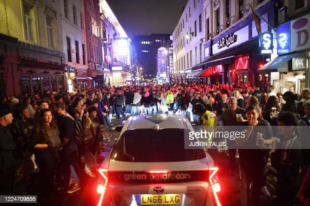 TOPSHOT A car tries to drive along a street filled with revellers drinking in the Soho area of London on July 4 after the police reopened the road at...