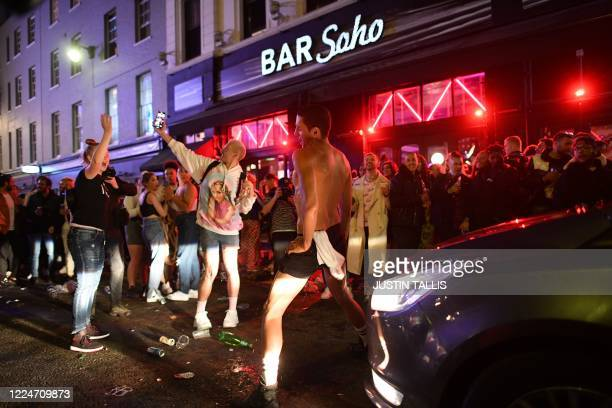 Car tries to drive along a street filled with revellers drinking in the Soho area of London on July 4 after the police re-opened the road at 2300 as...