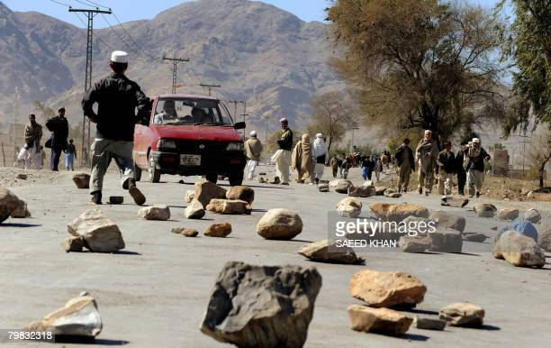 A car tries to makes its way through rocks on the road during a protest against election results in one of the tribal area constituencies in...
