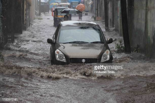 A car wades through a waterlogged road due to heavy rain on June 28 2019 in Kalyan India At least four persons including a minor boy were killed and...