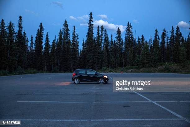 car waiting with lights on for hikers at banff national park, canada - christina felschen stock photos and pictures