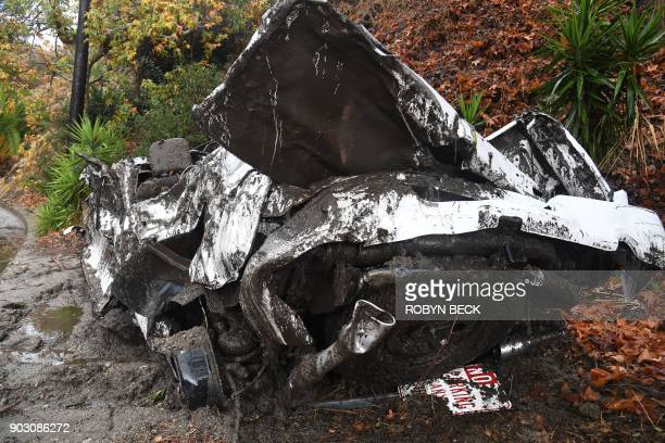 A car washed downhill in a raindriven mudslide are seen in a neighborhood under mandatory evacuation in Burbank California January 9 2018 Mudslides...