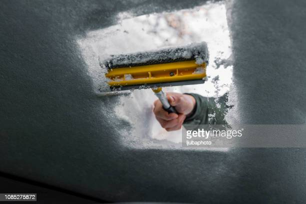 car window being cleared of snow with an ice scraper - scraping stock photos and pictures